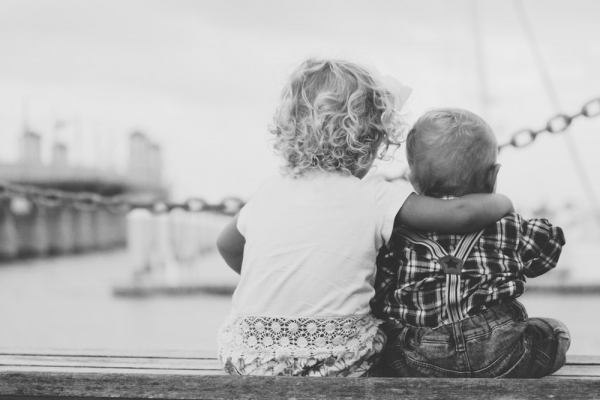 Two young children sit on a dock edge, arm wrapped around the other in black and white photo